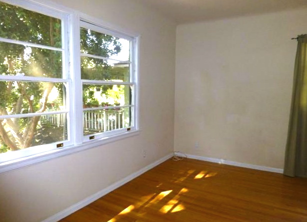Bedroom with double hung windows and original wood floors