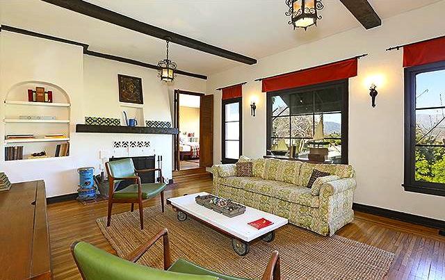 Living room with beamed ceiling, original windows, original wood floors and views