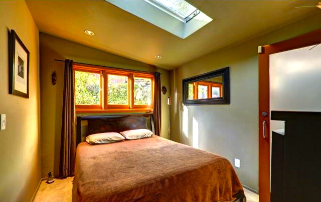 Bedroom with vaulted ceiling and skylight