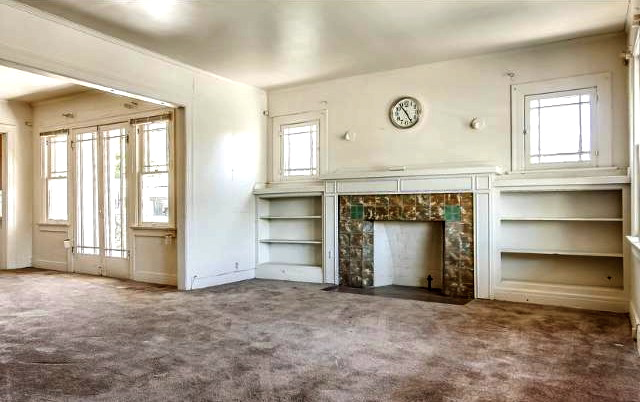 Living room, fireplace, built-ins and original wood floors beneath