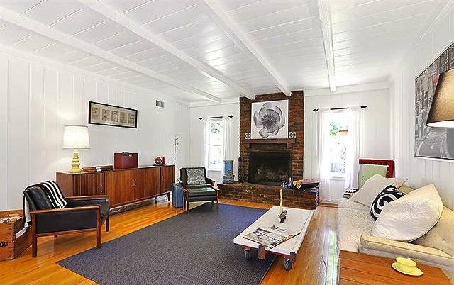Living room with beamed ceiling and original wood floors