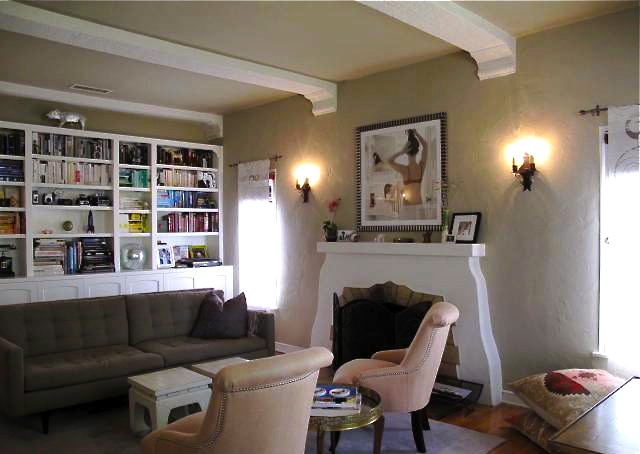 Living room with wood floors, beamed ceiling and fireplace