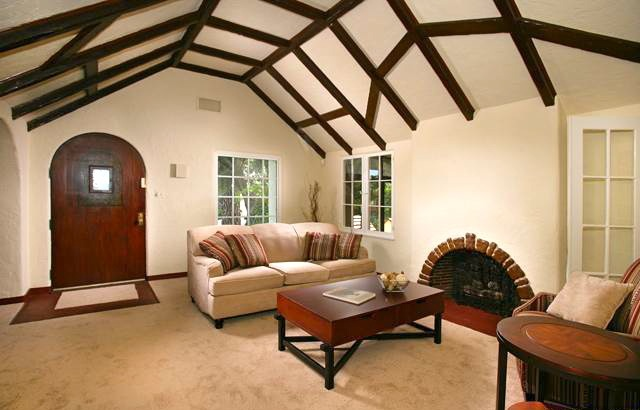 Living room with beamed ceiling, fireplace and original hardwood underneath