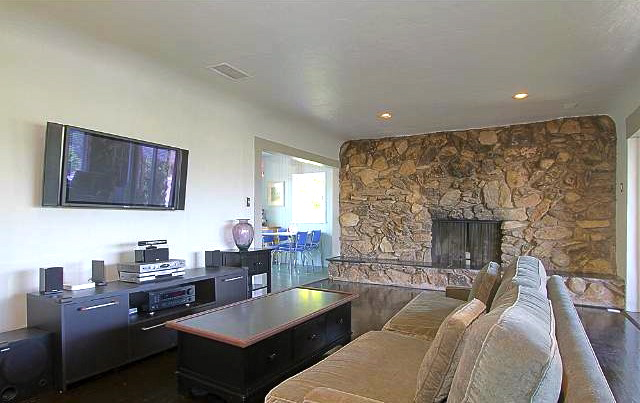 Living room with wood floors and stone wall fireplace