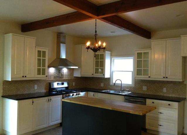 Kitchen with beamed ceiling and custom tile backsplash