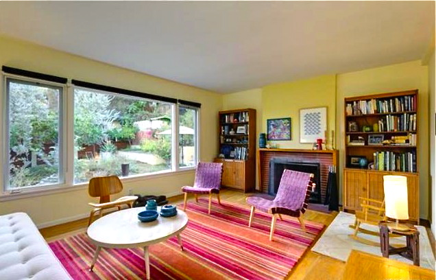 Living room with original wood floors, fireplace and picture window