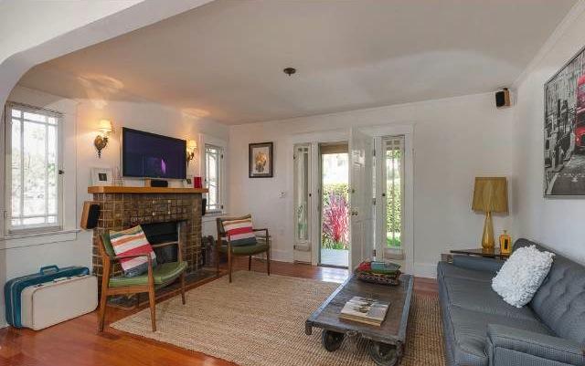 Living room with wood floors, Batchelder fireplace and casement windows