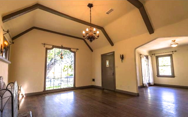 Living room with barreled beamed ceiling, leaded glass picture window and original wood floors