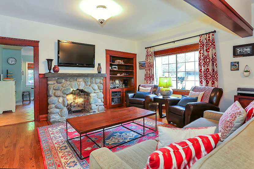 Living room with original wood floors, river rock fireplace and built-ins