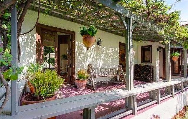 Pergola-flanked porch with mature vines. Courtesy of Scott Stephens – Keller Williams